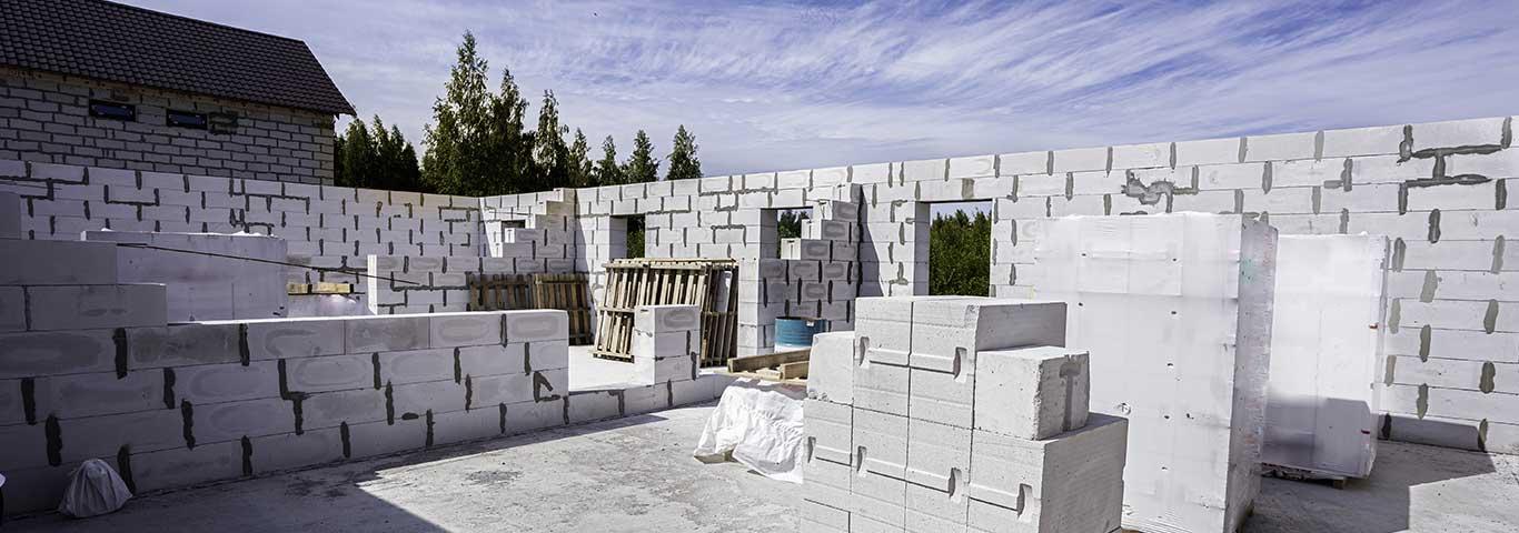 beton komórkowy wyłożony na palecie na tle budowy domu