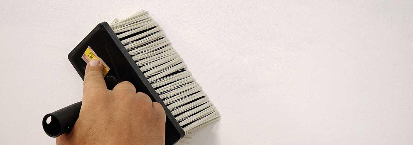 specjalista oczyszcza ścianę z kurzu