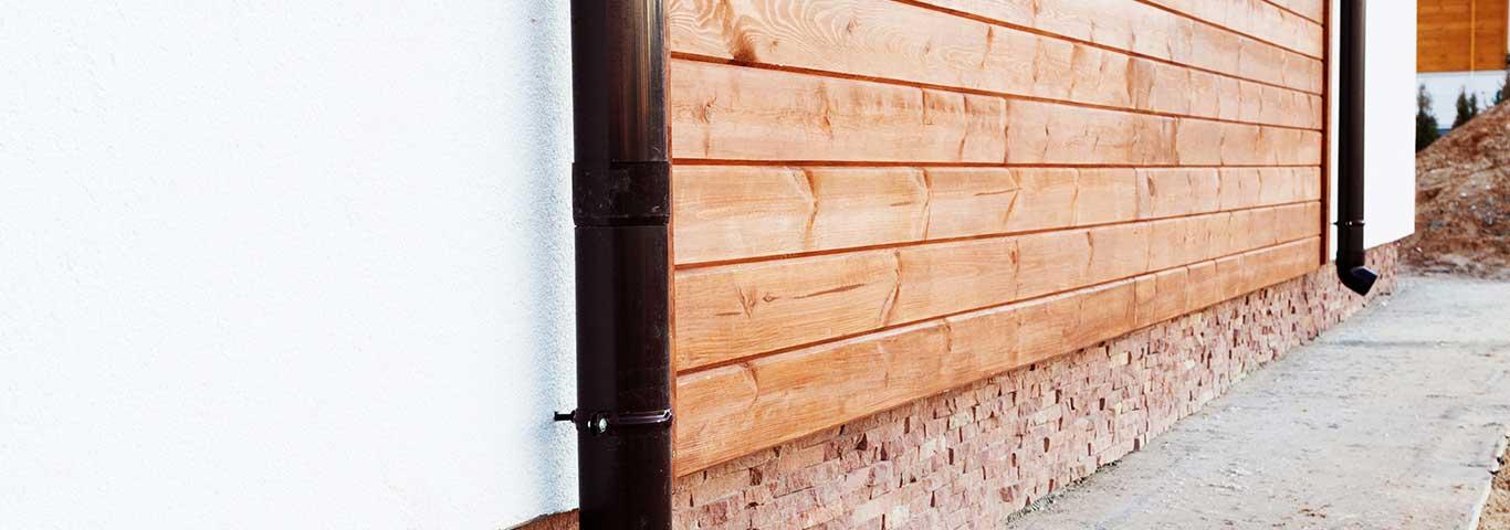 drewniane deski elewacyjne na białej ścianie nowego domu