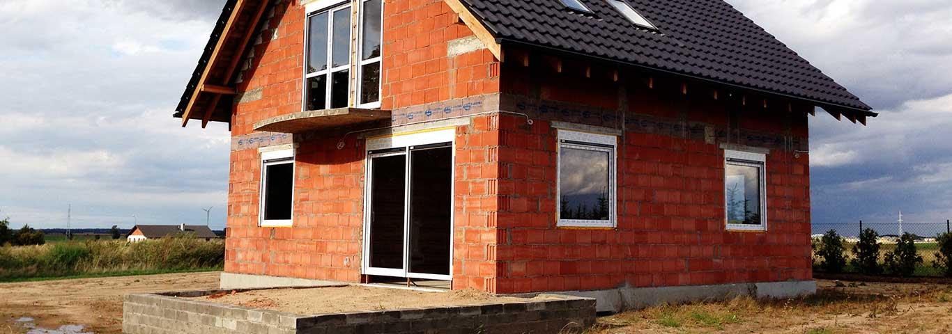 dom w stanie surowym zamkniętym z białymi oknami