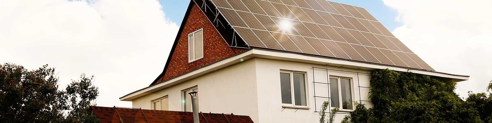panele fotowoltaiczne odbijające światło na dachu domu