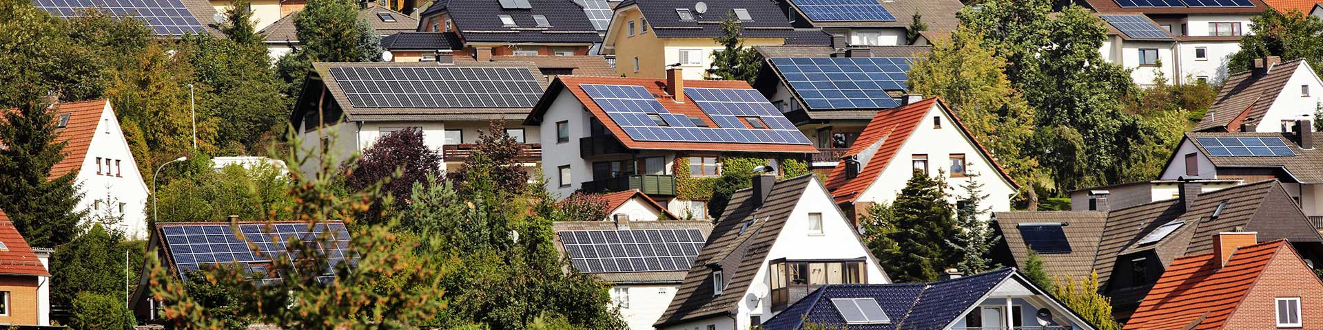 domy z zainstalowanymi na dachach panelami fotowoltaicznymi