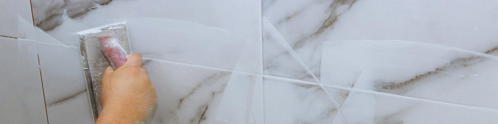 glazurnik wypełnia białą fugą  spoiny między płytkami