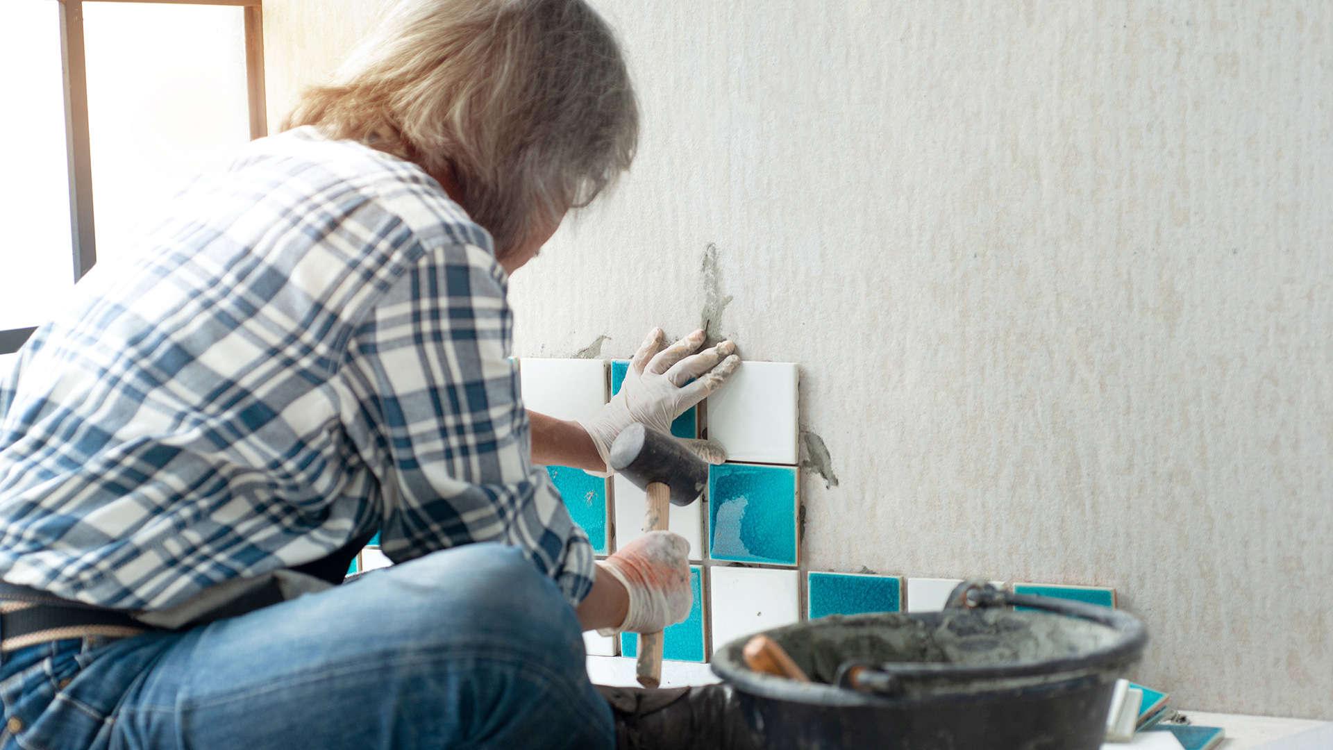 glazurnik dobija młotkiem gumowym kolorowe płytki ułożone na ścianie -  w 2021
