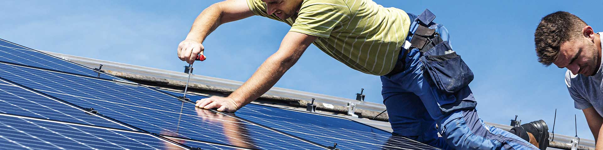 technik paneli słonecznych instaluje panele słoneczne na dachu