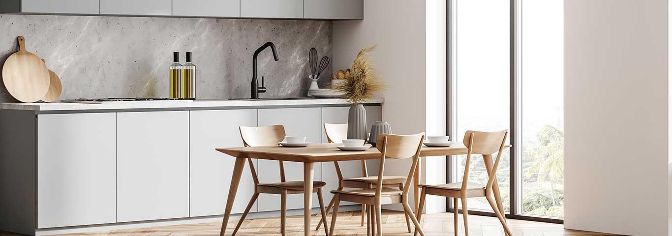 szare meble i drewniany stół z krzesłami we wnętrzu minimalistycznej kuchni