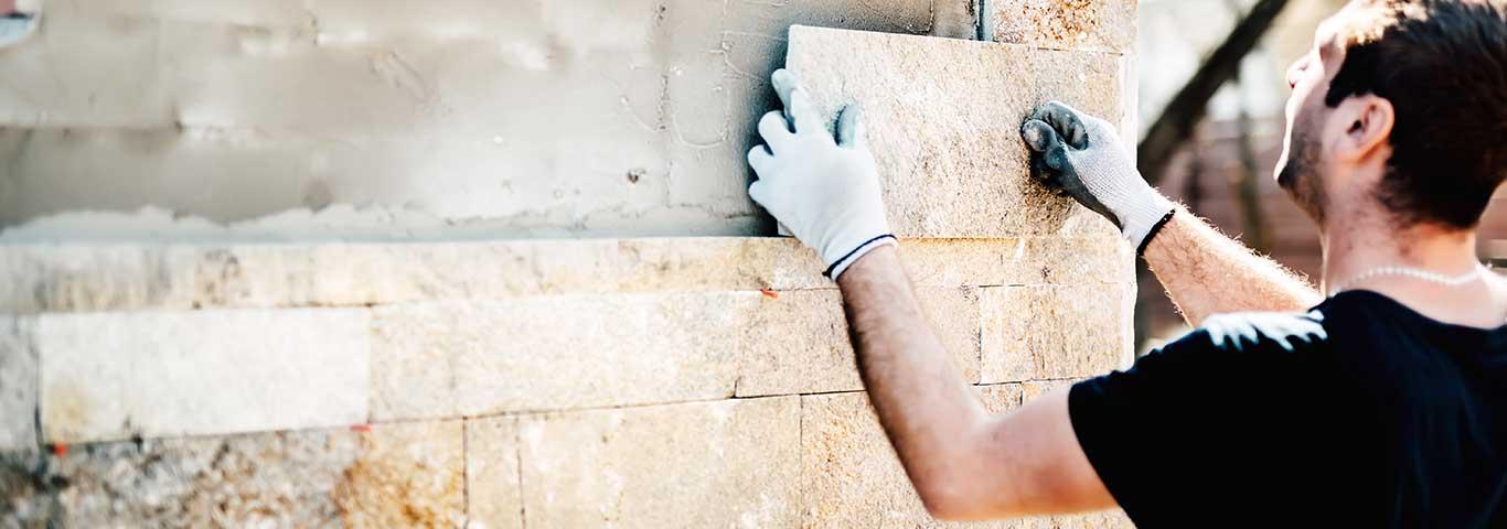 specjalista od tynkowania instaluje kamienne płytki na elewacji domu