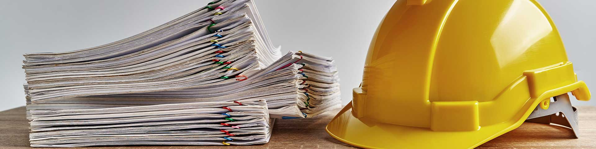 kask budowlany i stos dokumentów leżące na stole