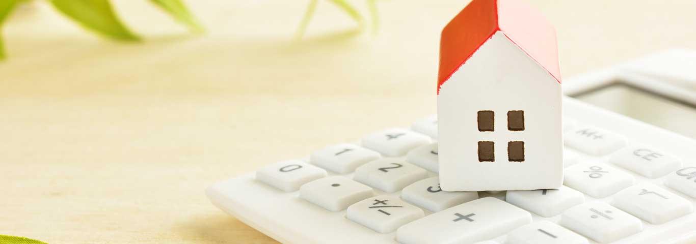 makieta domu stojąca na kalkulatorze