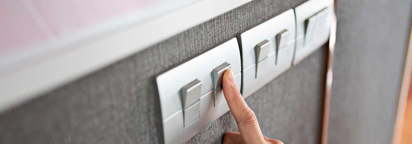 dłoń kobiety naciska przycisk łącznika schodowego