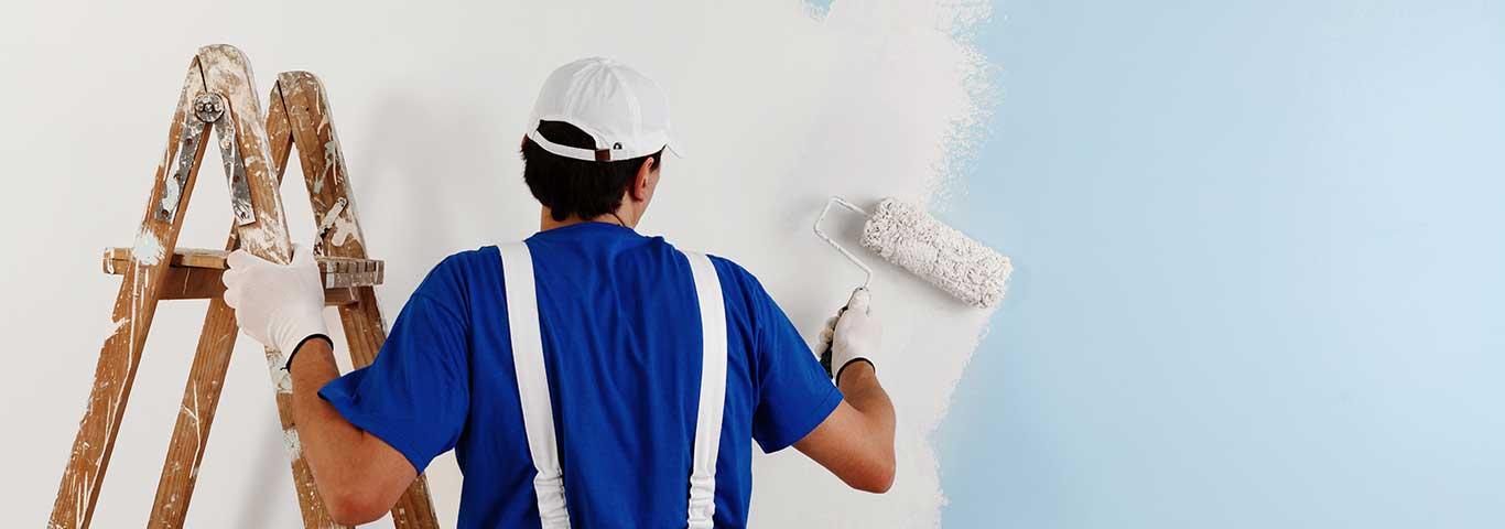 malarz maluje ścianę wałkiem na biało