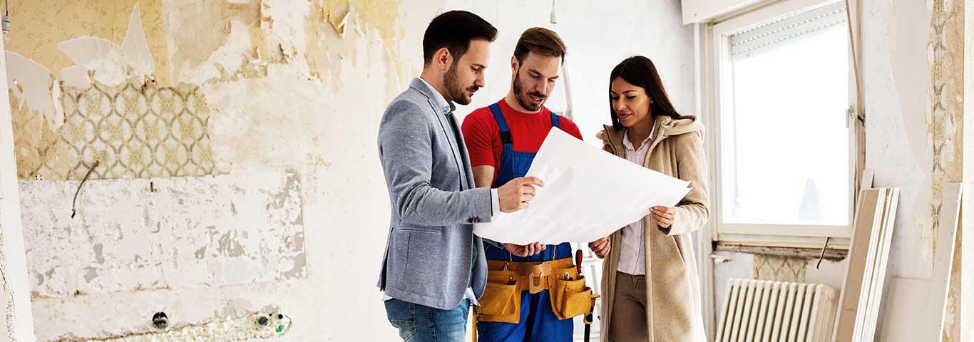 mężczyzna i kobieta rozmawiają z budowlańcem trzymając dokument