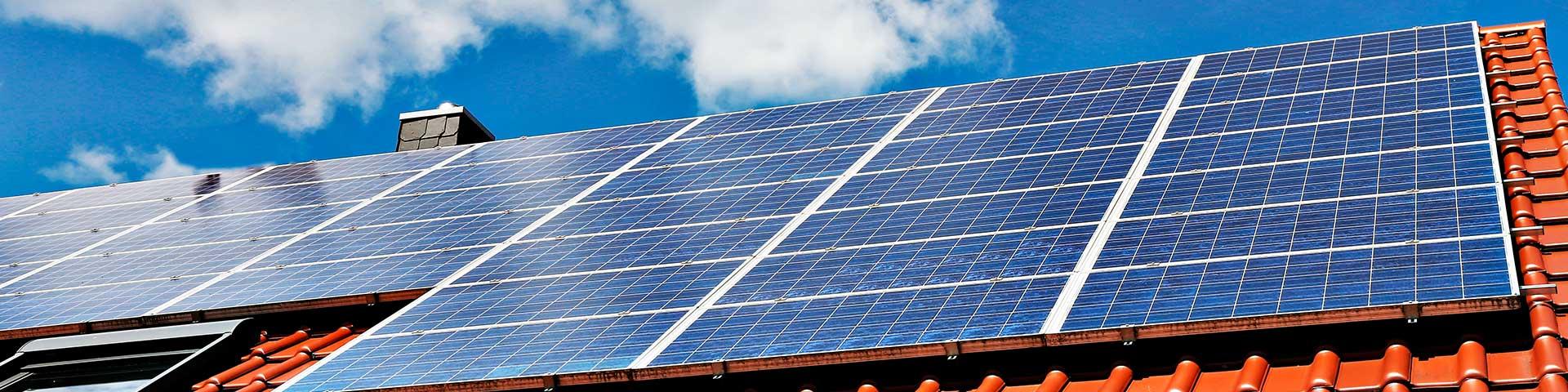 panele fotowoltaiczne na dachu z dachówki w czerwonym kolorze