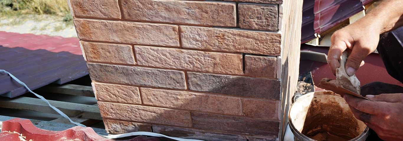 specjalista przygotowuje zaprawę murarską do pokrycia łączeń komina
