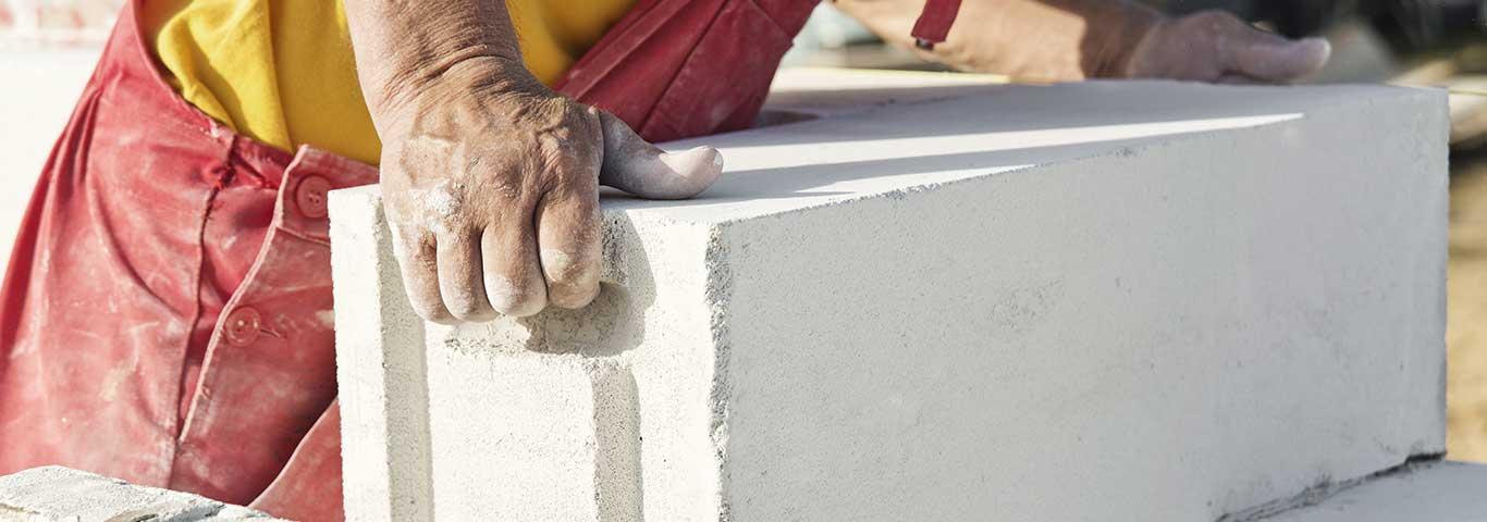 specjalista zakłada bloczek z betonu komórkowego na pozostałe bloczki