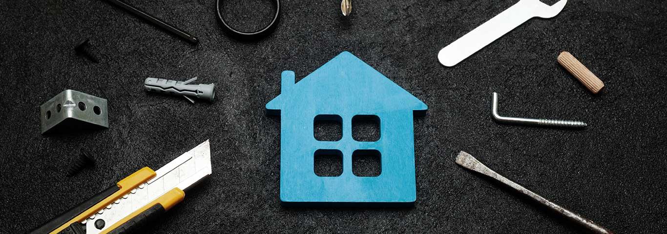 model niebieskiego domku położony na czarnym tle z narzędziami budowlanymi