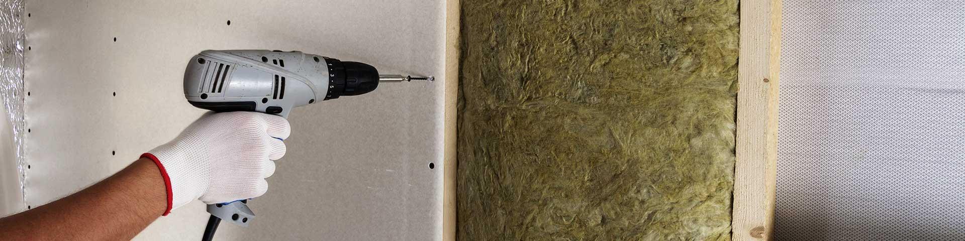 pracownik mocuje elektrycznym śrubokrętem płyty gipsowo-kartonowe