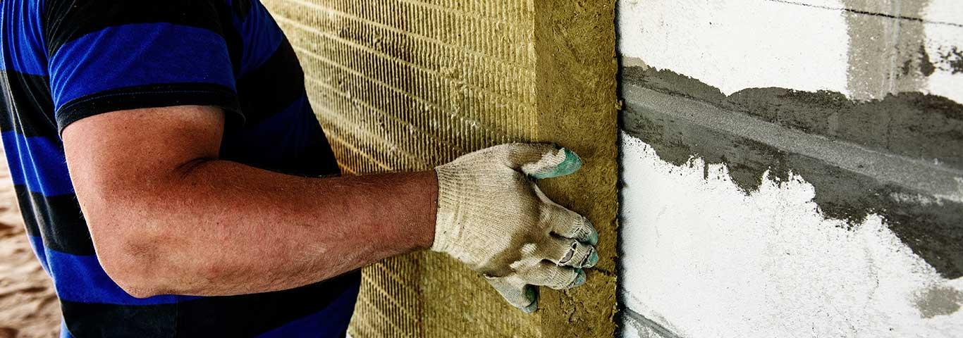 pracownik izoluje dom płytami z wełny mineralnej