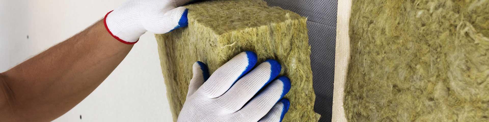 pracownik w białych rękawiczkach wykonuje izolację z wełny mineralnej