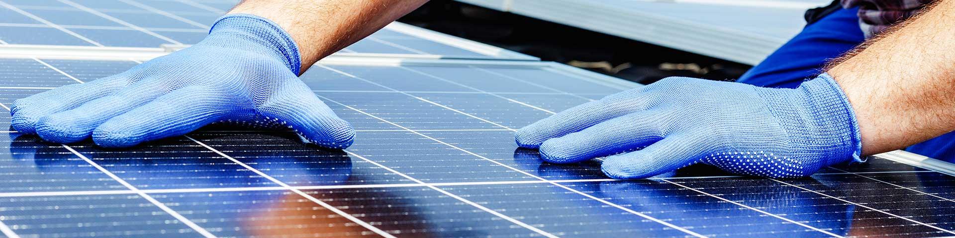 zbliżenie na instalatora montującego panele słoneczne na dachu