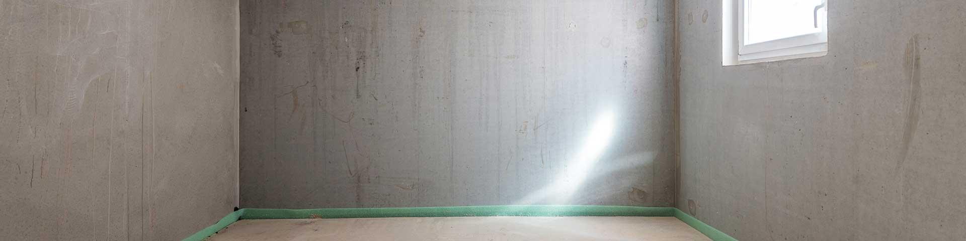 pusta piwnica z betonowymi ścianami i białym oknem gospodarczym