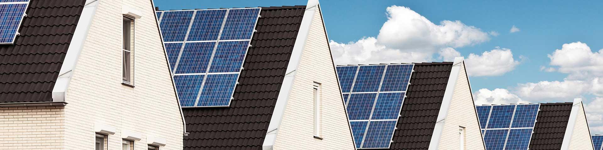 rząd nowych domów z panelami fotowoltaicznymi na dachu