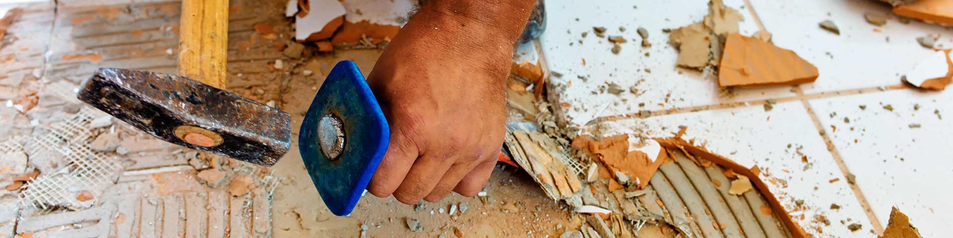 glazurnik skuwa płytki na podłodze za pomocą młotka i przebijaka