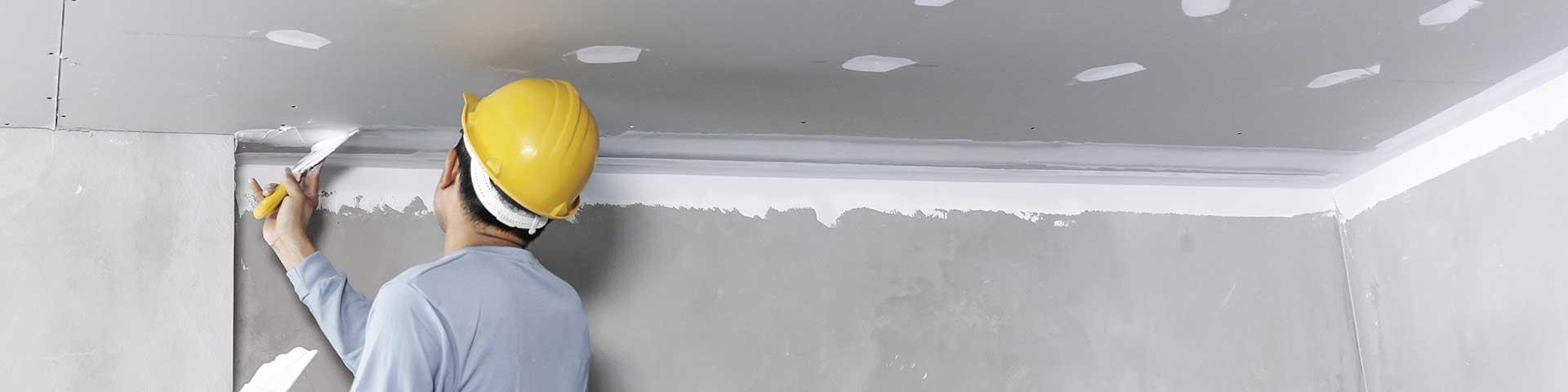 specjalista od remontów wykańcza sufit podwieszany z płyt gipsowo-kartonowych