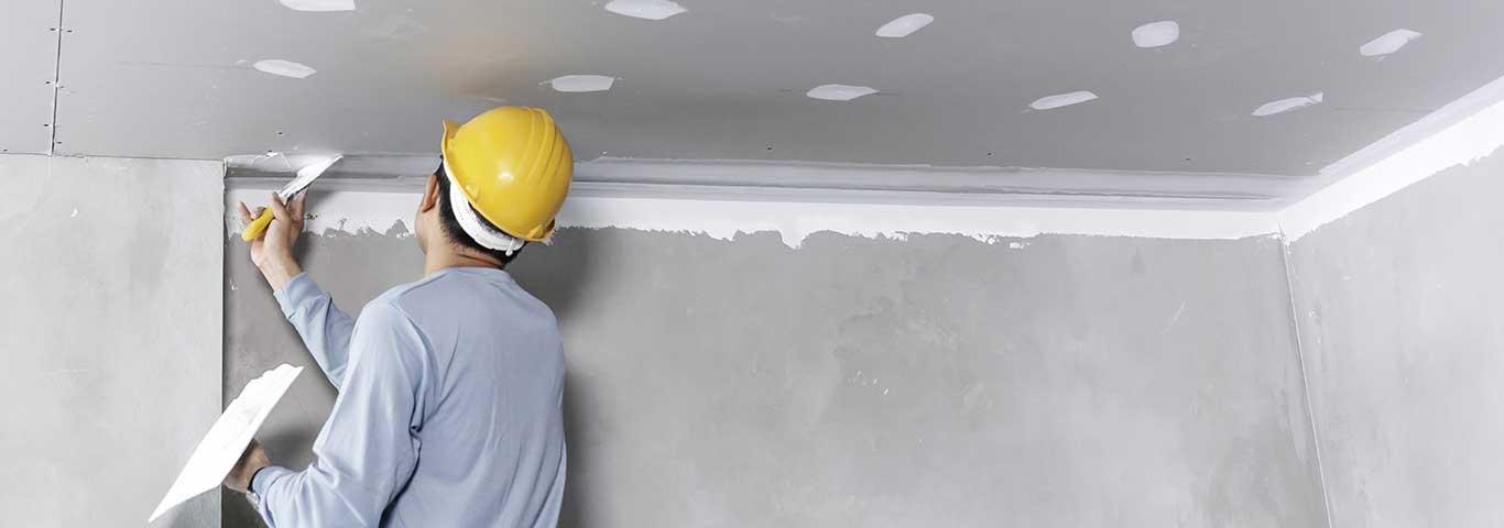fachowiec wykańcza sufit podwieszany z płyt gipsowo-kartonowych