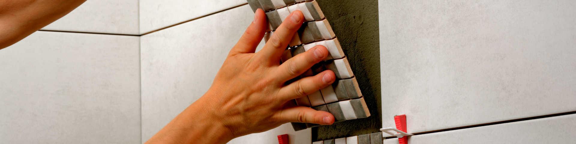 glazurnik układa płytki na ścianie, wykorzystując klipsy i kliny do poziomowania płytek