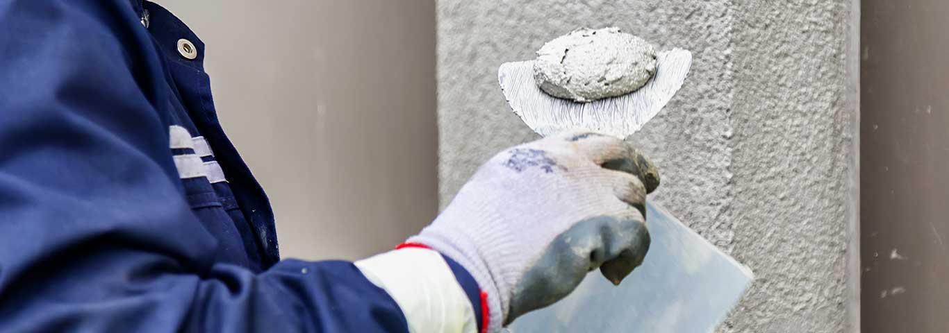 tynkarz trzyma w ręku pacę stalową z tynkiem