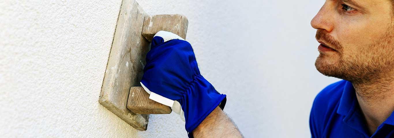 specjalista od tynkowania nakłada kielnią tynk na zewnętrzną ścianę domu