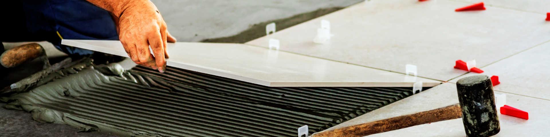 glazurnik układa na podłodze płytki wielkoformatowe