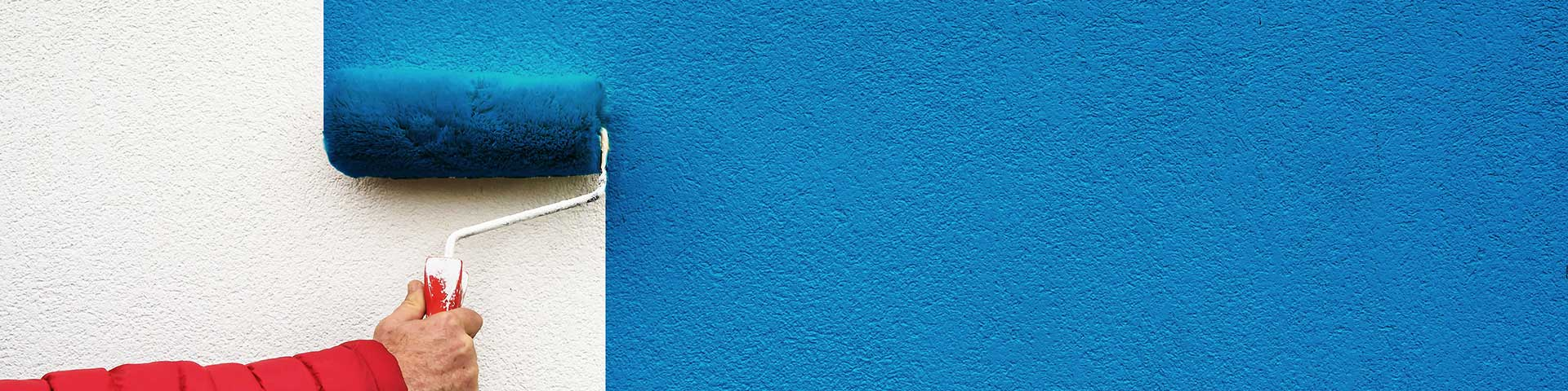 mężczyzna maluje ścianę wałkiem na niebiesko