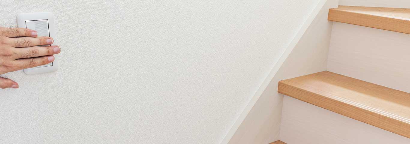 dłoń mężczyzny naciska przycisk na łączniku schodowym