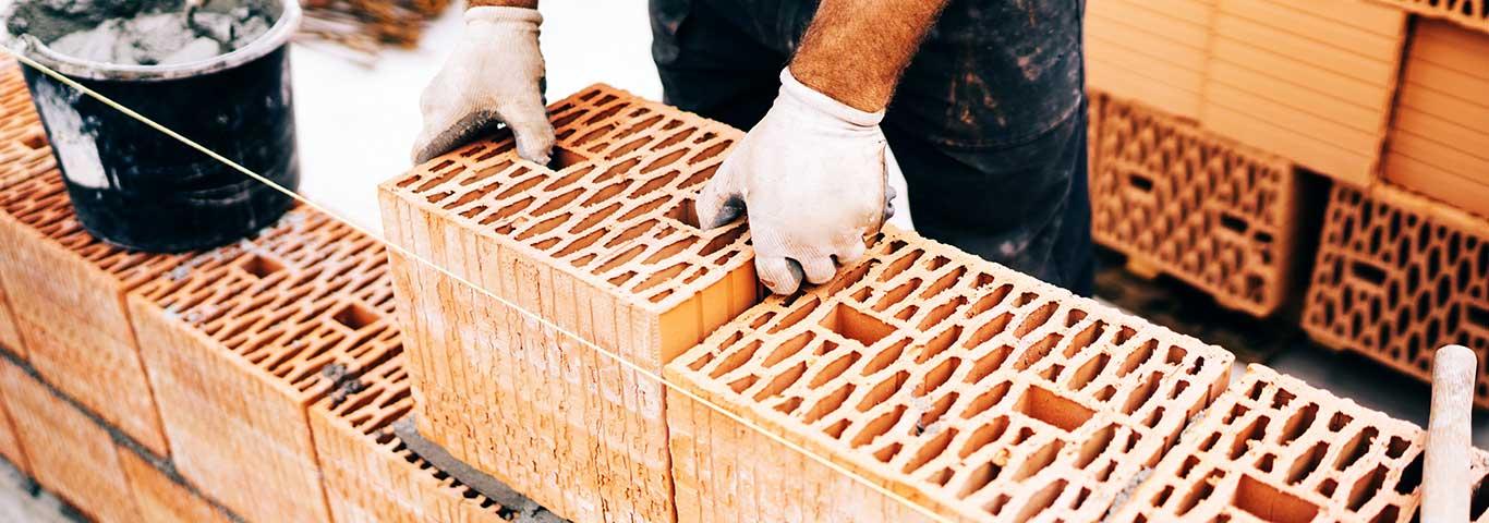 mężczyzna buduje ścianę domu z pustaków ceramicznych