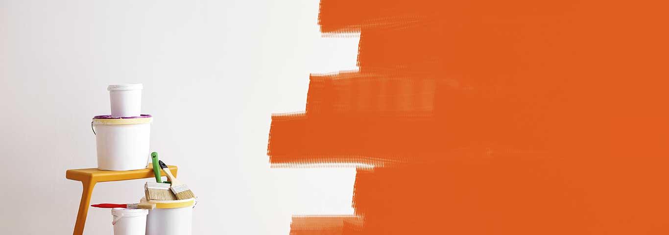 zestaw niezbędnych narzędzi i farb do malowania ścian na tle pomarańczowej ściany