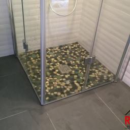 Kabina prysznicowa z odpływem punktowym a w powierzchni prysznicowej wklejone kamyczki.