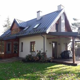 Mały budynek z użytkowym poddaszem dopasowany do niewielkiej działki. Dom z drewnianymi ozdobami kontrastujący z jasną elewacją i ciemnym dachem wkomponowany w otaczające go sąsiedztwo.