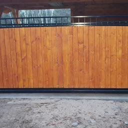 Brama przesuwna kuta wypełnienie drewno.