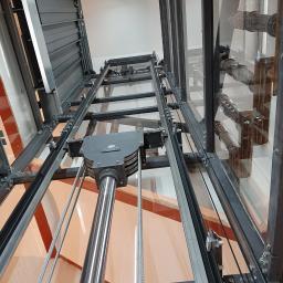 dźwig hydrauliczny w przeszklonej konstrukcji samonośnej zamontowany na klatce schodowej zabytkowego budynku