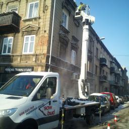 Podnośnik 24m , praca przy usuwaniu nawisów śnieżnych na dachach kamienic.