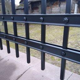 Przęsło wykonane z płaskownika i pręta kwadratowego imitacja nitowanego ogrodzenia pomalowana proszkowo.